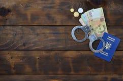 A photograph of a Ukrainian foreign passport, a certain amount of Ukrainian money and police handcuffs. Concept of illegal earnin. Gs of Ukrainian citizens royalty free stock photos