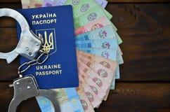 A photograph of a Ukrainian foreign passport, a certain amount of Ukrainian money and police handcuffs. Concept of illegal earnin. Gs of Ukrainian citizens stock images