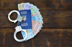 A photograph of a Ukrainian foreign passport, a certain amount of Ukrainian money and police handcuffs. Concept of illegal earnin. Gs of Ukrainian citizens stock photo