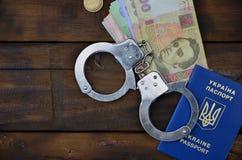 A photograph of a Ukrainian foreign passport, a certain amount of Ukrainian money and police handcuffs. Concept of illegal earnin. Gs of Ukrainian citizens stock photos