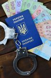 A photograph of a Ukrainian foreign passport, a certain amount of Ukrainian money and police handcuffs. Concept of illegal earnin. Gs of Ukrainian citizens royalty free stock images