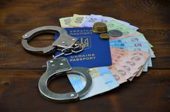 A photograph of a Ukrainian foreign passport, a certain amount of Ukrainian money and police handcuffs. The concept of arresting. Ukrainian illegal immigrants royalty free stock images