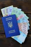 A photograph of a Ukrainian passport and a certain amount of Ukrainian money on a wooden surface. The concept of making money for. Ukrainian citizens abroad royalty free stock photos