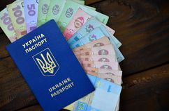 A photograph of a Ukrainian passport and a certain amount of Ukrainian money on a wooden surface. The concept of making money for. Ukrainian citizens abroad stock photography