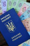 A photograph of a Ukrainian passport and a certain amount of Ukrainian money on a wooden surface. The concept of making money for. Ukrainian citizens abroad royalty free stock photo