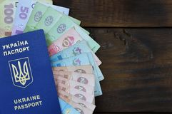 A photograph of a Ukrainian passport and a certain amount of Ukrainian money on a wooden surface. The concept of making money for. Ukrainian citizens abroad royalty free stock photography