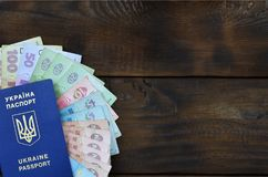 A photograph of a Ukrainian passport and a certain amount of Ukrainian money on a wooden surface. The concept of making money for. Ukrainian citizens abroad stock photos