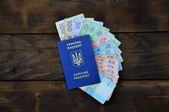 A photograph of a Ukrainian passport and a certain amount of Ukrainian money on a wooden surface. The concept of making money for. Ukrainian citizens abroad royalty free stock image