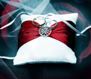 Photograph of wedding rings on white pillow with red ribbon Royalty Free Stock Image