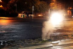 Sewer steam in a cold night in Budapest. Photograph where the cold of the night is reflected in the steam coming out of the sewer system illuminated by the royalty free stock photography