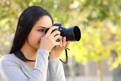 Photograph woman learning photography in a park. Happy with a green unfocused background Royalty Free Stock Photos