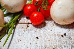 On a wooden bleached tabletop lies a set of vegetables for cooking. On a photograph on a wooden table painted in white paint lie a set of vegetables for cooking stock image