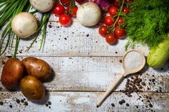 On a wooden bleached tabletop lies a set of vegetables for cooking. On a photograph on a wooden table painted in white paint lie a set of vegetables for cooking stock photos