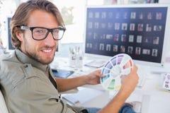 Photographe éditeur regardant la roue de couleur et se tournant vers le sourire images stock