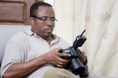 Photographe africain regardant l'écran de son appareil photo numérique photo stock