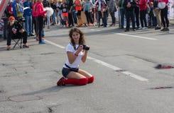 Photographe amateur féminin mignon s'asseyant sur une rue et attendant un finisseur pour pour faire le tir frais Photographie stock libre de droits