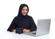 Photographe Arabe travaillant sur son ordinateur portable au bureau Images stock