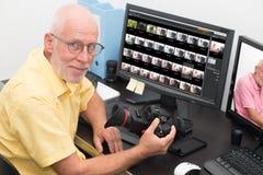 Photographe avec l'appareil-photo au bureau avec l'ordinateur image stock