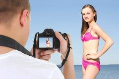 Photographe avec l'appareil-photo de dslr prenant la photo de la belle femme Photographie stock libre de droits
