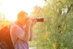Photographe avec l'appareil-photo de SLR et sac à dos en nature, vue de côté Photographie stock libre de droits