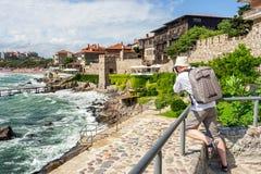 Photographe avec le tir de sac à dos dans la vieille ville Sozopol près de la mer images libres de droits