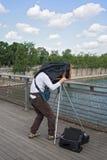 Photographe avec le vieil appareil-photo de plat sur le pont en seine Passerelle Solferino à Paris Photographie stock libre de droits