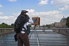 Photographe avec le vieil appareil-photo de plat sur le pont en seine Passerelle Solferino à Paris Photos libres de droits