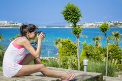 Photographe de jeune femme prenant des photos dans un jardin tropical vert avec la vue de mer Photos stock