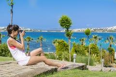 Photographe de jeune femme prenant des photos dans un jardin tropical vert avec la vue de mer Images stock