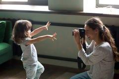 Photographe de maman faisant la photo de la fille d'enfant sur l'appareil photo numérique photo stock