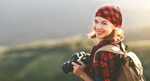 Photographe de touristes de femme avec l'appareil-photo sur la montagne au soleil Photographie stock