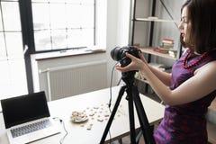 Photographe féminin accordant son appareil-photo au studio photographie stock libre de droits