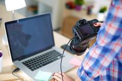 Photographe féminin s'asseyant sur le bureau avec image libre de droits