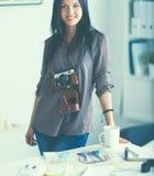 Photographe féminin s'asseyant sur le bureau avec l'ordinateur portable photographie stock