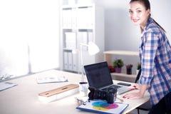 Photographe féminin s'asseyant sur le bureau avec l'ordinateur portable Photographe féminin Image libre de droits