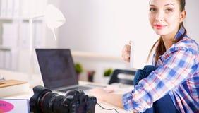 Photographe féminin s'asseyant sur le bureau avec l'ordinateur portable Image libre de droits