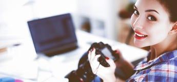 Photographe féminin s'asseyant sur le bureau avec l'ordinateur portable photo stock