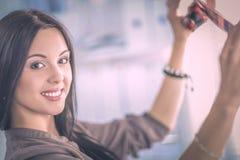 Photographe féminin s'asseyant sur le bureau avec l'ordinateur portable photos stock