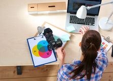 Photographe féminin s'asseyant sur le bureau avec l'ordinateur portable Images stock