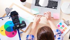 Photographe féminin s'asseyant sur le bureau avec l'ordinateur portable Photos libres de droits