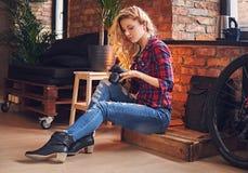 Photographe femelle blond amateur prenant des photos dans une chambre avec Image libre de droits