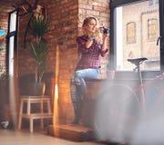 Photographe femelle blond amateur prenant des photos dans une chambre avec Photographie stock libre de droits