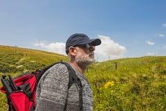 Photographe mûr d'homme dans le chapeau avec le trekking rouge de sac à dos en Ecosse image libre de droits