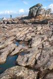 Photographe marchant sur le bord de la mer en pierre Photo stock