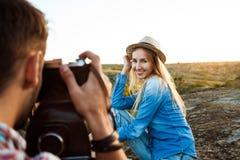 Photographe masculin beau prenant la photo de son amie, fond de canyon Images libres de droits