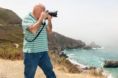 Photographe masculin prenant des photos à la falaise image stock