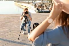 Photographe masculin prenant la photo de la jeune femme avec l'appareil-photo professionnel photo stock
