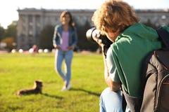 Photographe masculin prenant la photo de la jeune femme avec l'appareil-photo professionnel images stock