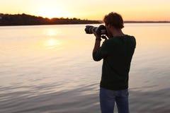 Photographe masculin prenant la photo du coucher du soleil de rive avec l'appareil-photo professionnel images stock