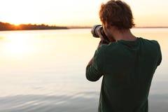 Photographe masculin prenant la photo du coucher du soleil de rive avec l'appareil-photo professionnel photographie stock libre de droits